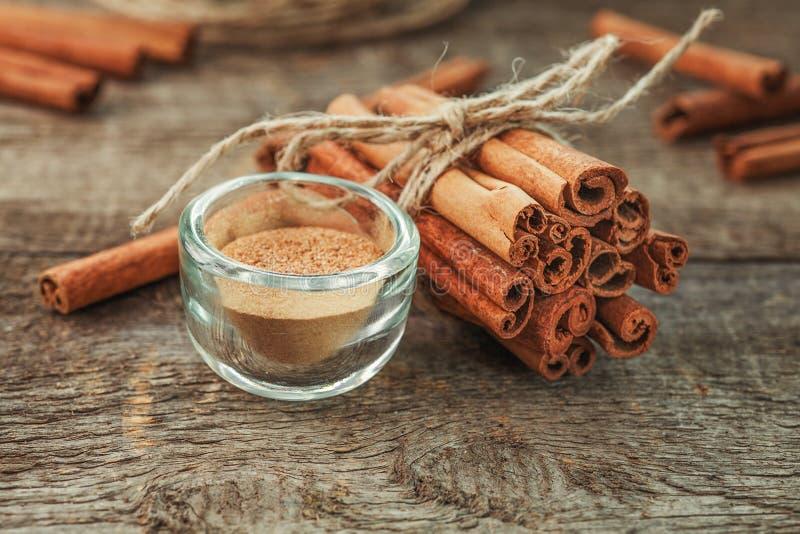 Canela à terra, varas de canela, amarradas com corda da juta no fundo de madeira velho no estilo rústico imagem de stock