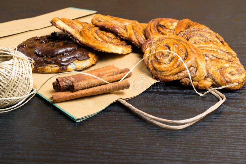 a canela doce caseiro, chocolate, papoila rola no saco de papel com as varas dos cinnamons desertos fotos de stock royalty free