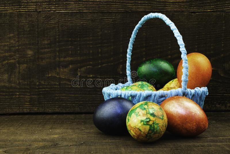 Canestro blu con le uova di Pasqua e le uova di Pasqua che si trovano vicino su un fondo di legno marrone scuro, spazio della cop immagini stock