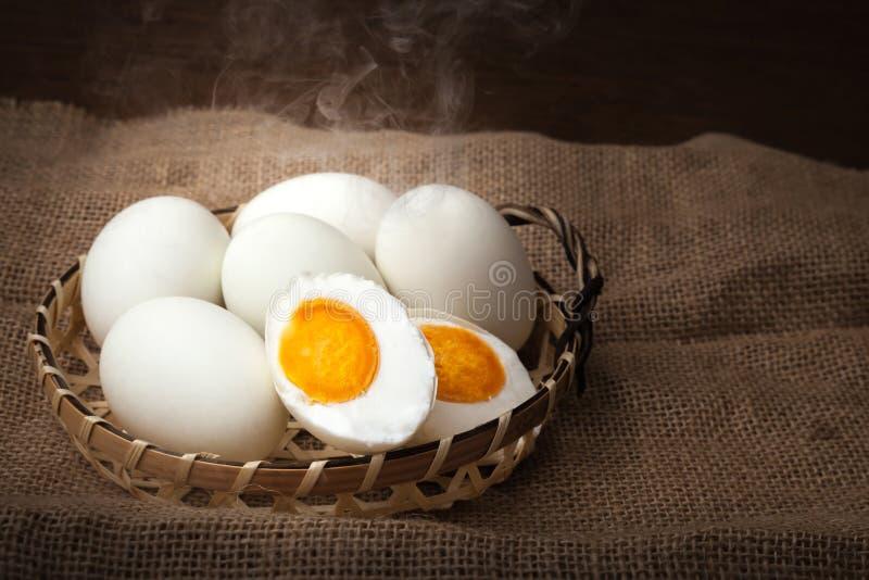 Canestro bollita e pronta da mangiare, sopra messo salato delle uova, fondo vago fotografia stock