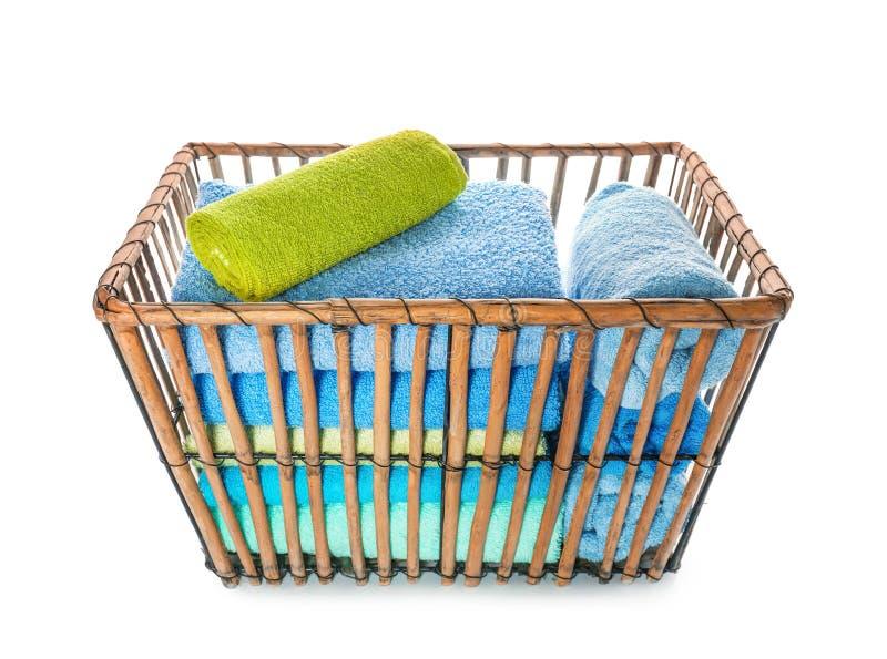 Canestro con gli asciugamani molli puliti su fondo bianco immagini stock