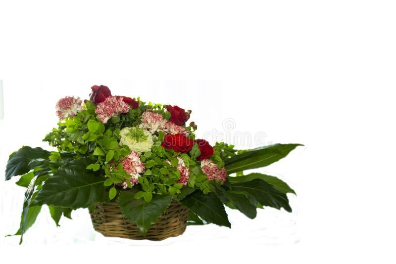 Canestro con i fiori: rose, garofani e fogliame fotografia stock libera da diritti