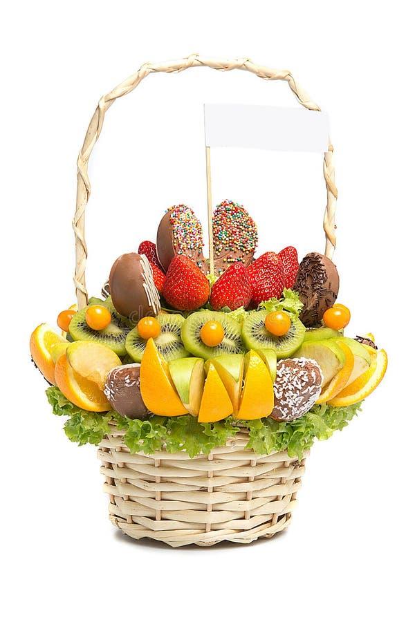 Canestro con i frutti e bacche in cioccolato isolato su fondo bianco handmade Fragole ed agrume, mela, kiwi fotografia stock libera da diritti