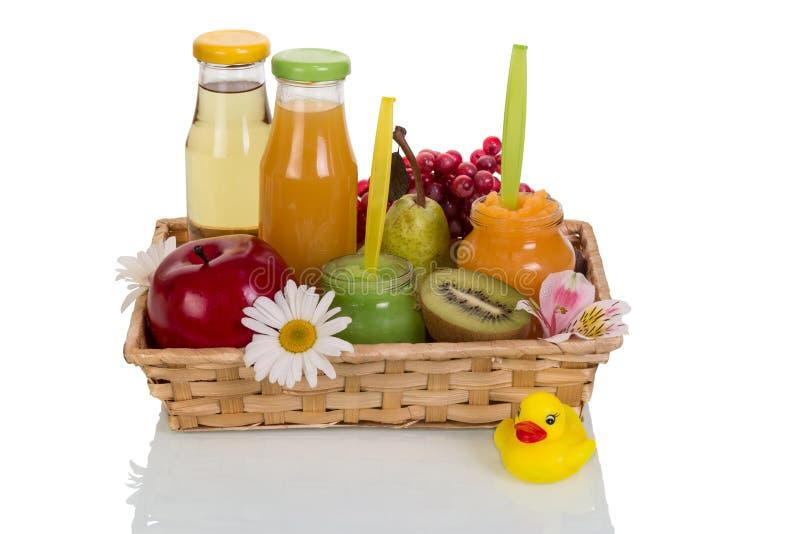 Canestro con i frutti e le bottiglie del succo immagini stock