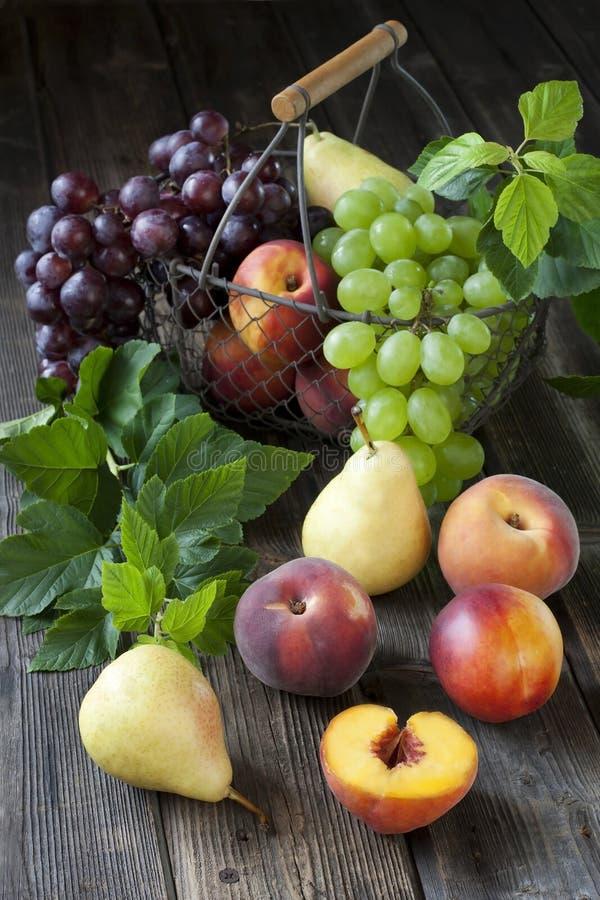 Canestro con le nettarine, le pesche, l'uva e le pere fotografia stock