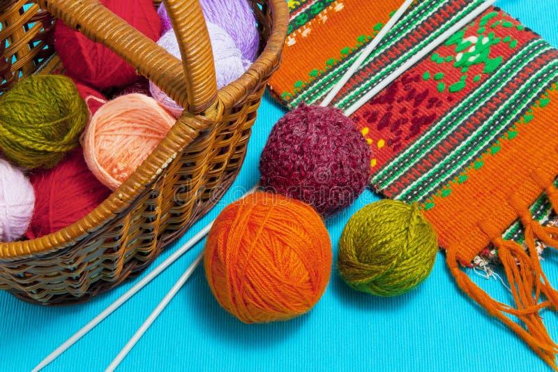 Canestro con le palle di lana e dei ferri da maglia su un fondo blu fotografia stock