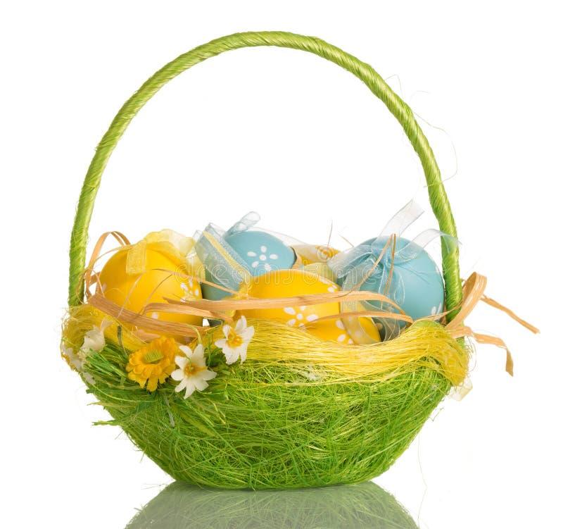 Canestro con le uova di Pasqua, isolate su bianco immagini stock libere da diritti