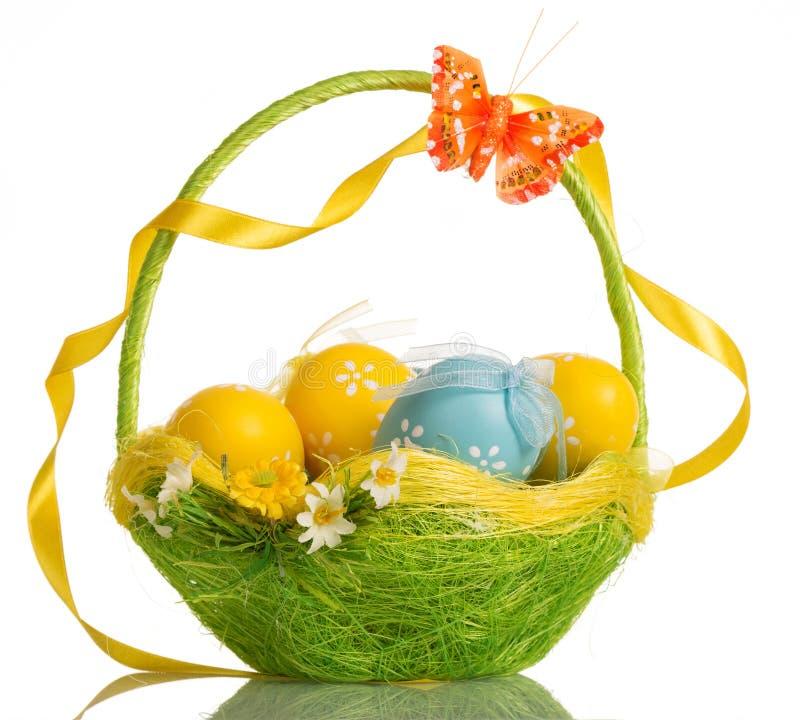 Canestro con le uova di Pasqua, la farfalla ed il nastro sulla maniglia, isolato immagine stock libera da diritti