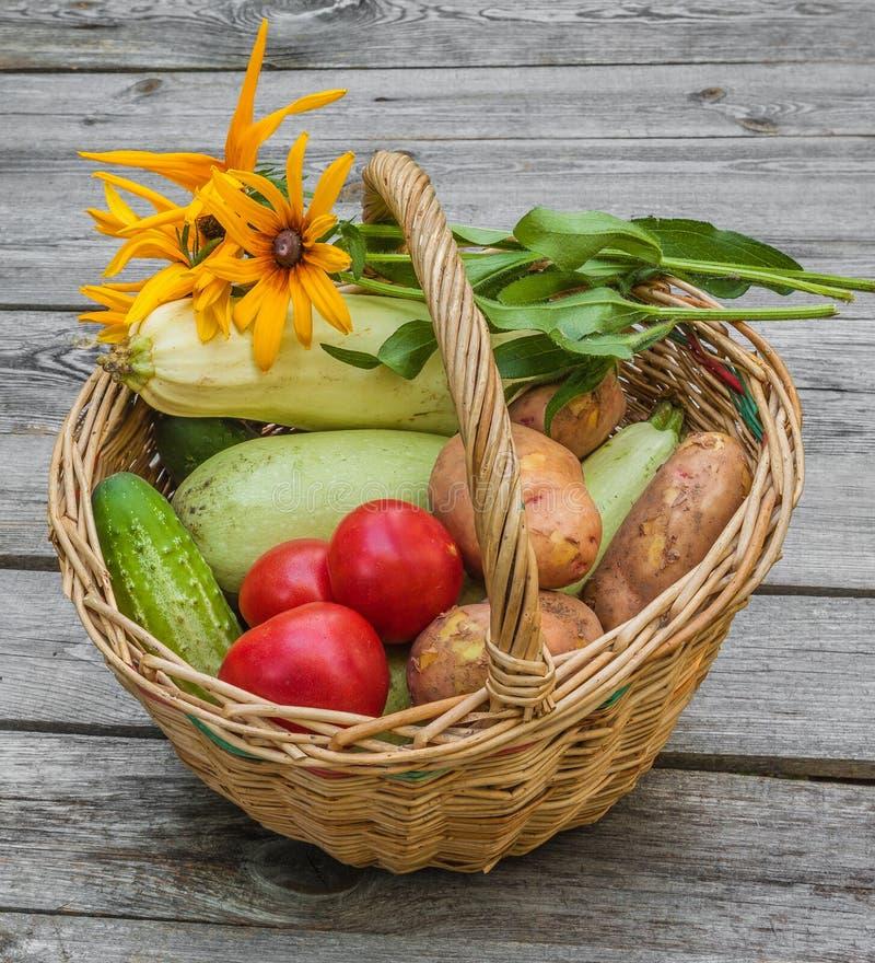 Canestro con le verdure e un mazzo di rudbeckia giallo fotografie stock libere da diritti