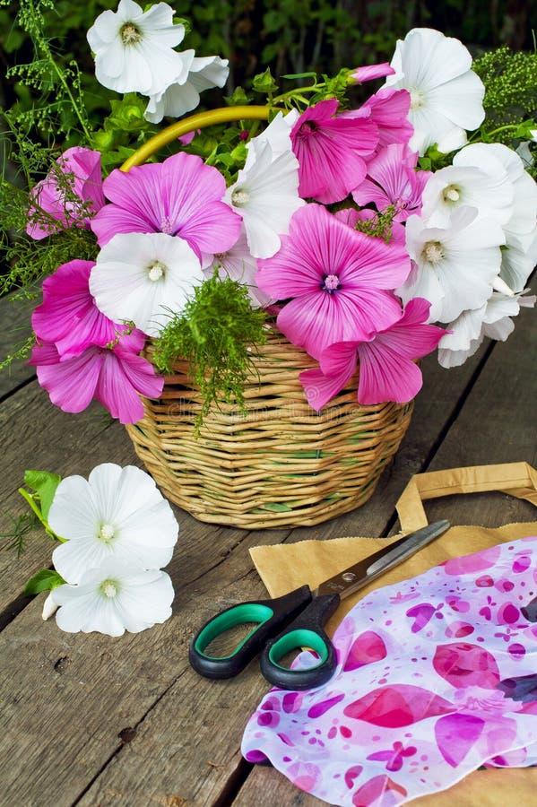 Canestro dei fiori su un fondo di legno Lavatera fotografie stock