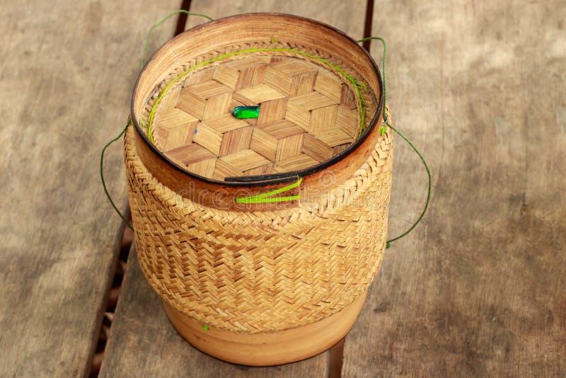 Canestro del riso, contenitore di bambù di tessuto per riso appiccicoso sulla vecchia parte posteriore di legno fotografie stock