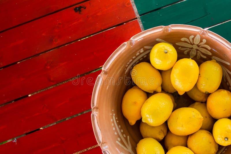 Canestro del vaso di argilla dei limoni sulla tavola coloful con copyspace fotografia stock
