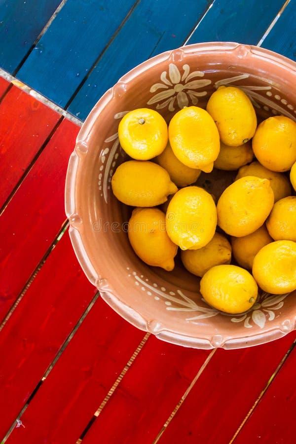 Canestro del vaso di argilla dei limoni sulla tavola coloful con copyspace fotografia stock libera da diritti