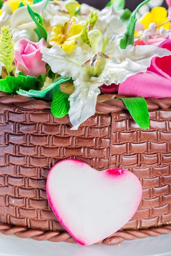Canestro delizioso del dolce con i vari fiori ed il cuore decorativo fotografie stock