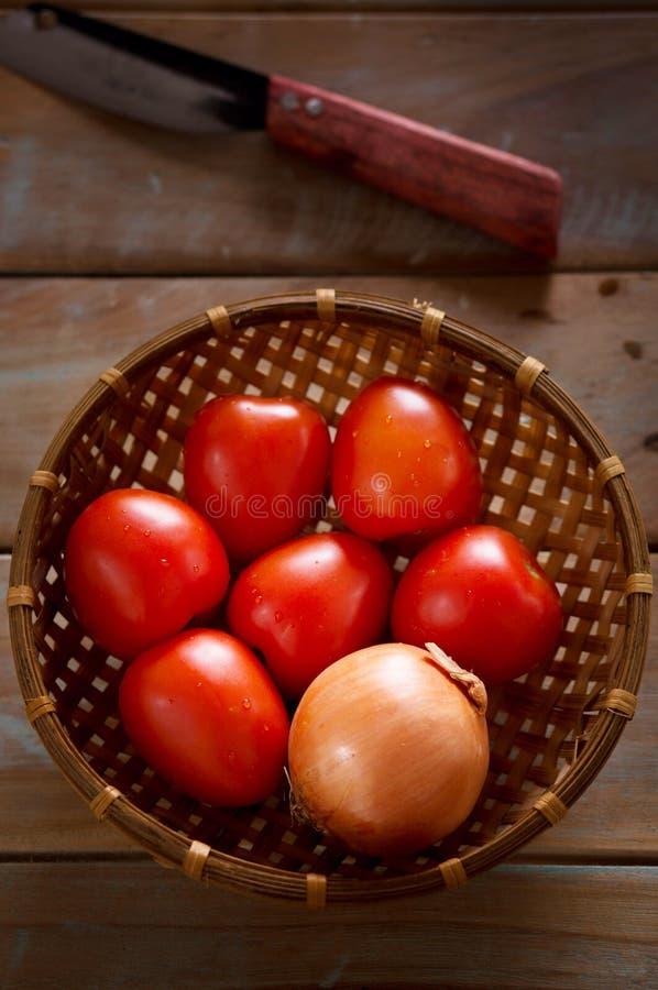 Canestro di bambù dei pomodori e della cipolla rossi con il coltello immagini stock