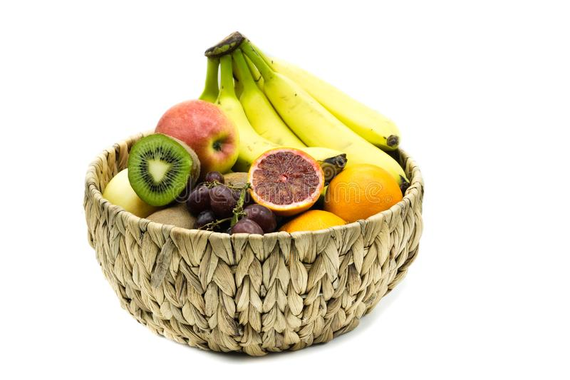 Canestro di frutta con le banane, le mele, le arance ed i kiwi isolati su fondo bianco fotografia stock
