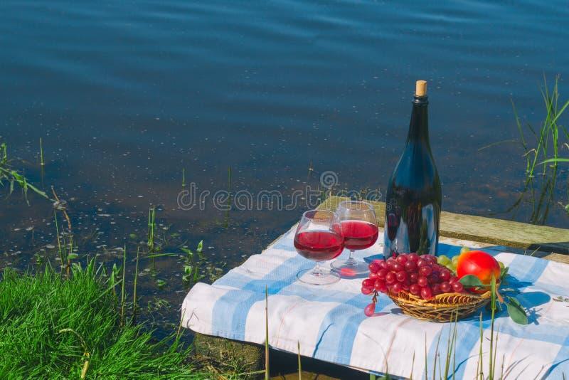 canestro di frutta e del vino, picnic sul lago e concetto di vacanze estive immagini stock