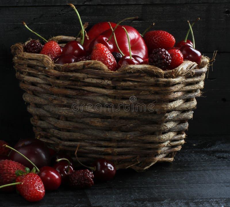 Canestro di frutti di legno su un fondo nero fotografia stock
