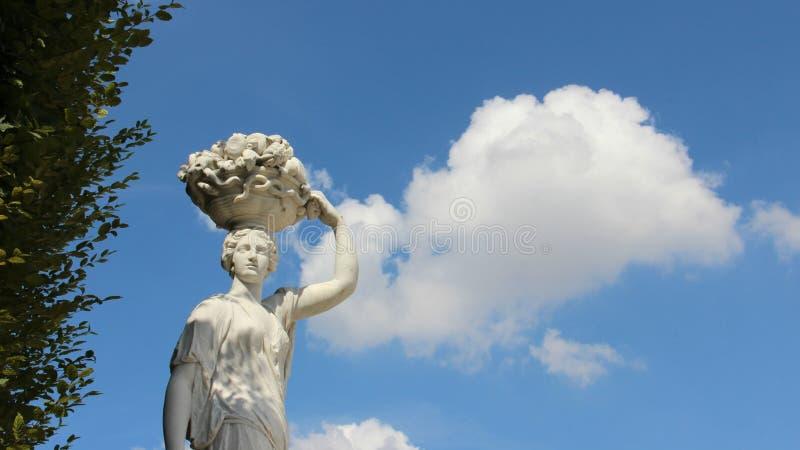 Canestro di frutti di trasporto della ragazza della scultura sulla sua testa immagini stock libere da diritti