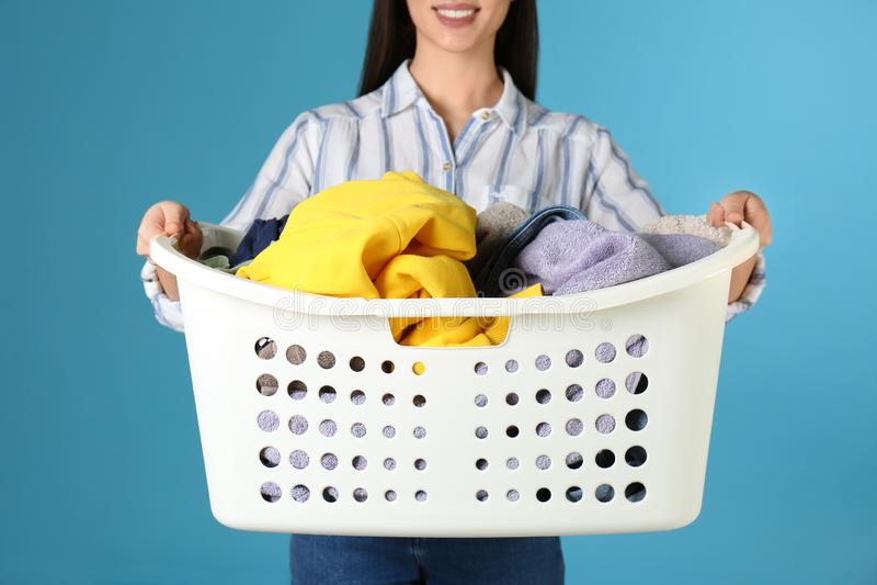 Canestro di lavanderia della tenuta della giovane donna con i vestiti sul fondo di colore fotografie stock