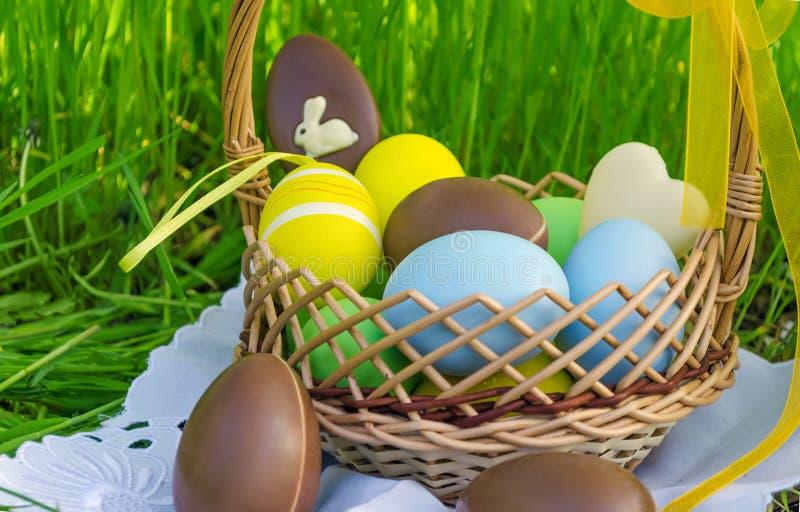 Canestro di Pasqua con le uova di cioccolato di pasqua e le uova colorate immagine stock libera da diritti