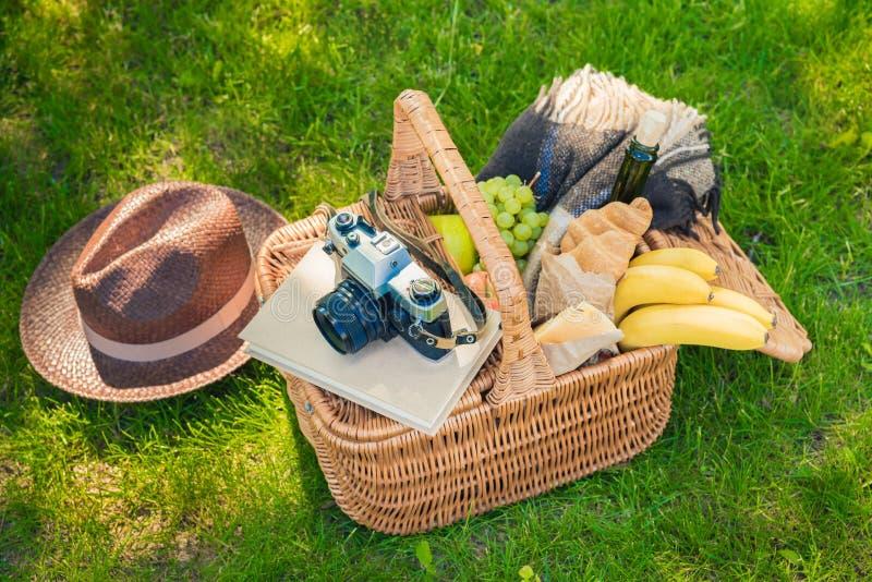 Canestro di picnic con lo spuntino saporito, il libro, la macchina fotografica d'annata ed il cappello su erba verde fotografia stock libera da diritti