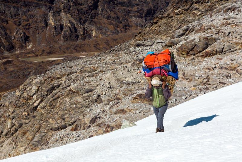 Canestro di trasporto del portatore nepalese con bagagli della spedizione della montagna fotografia stock libera da diritti