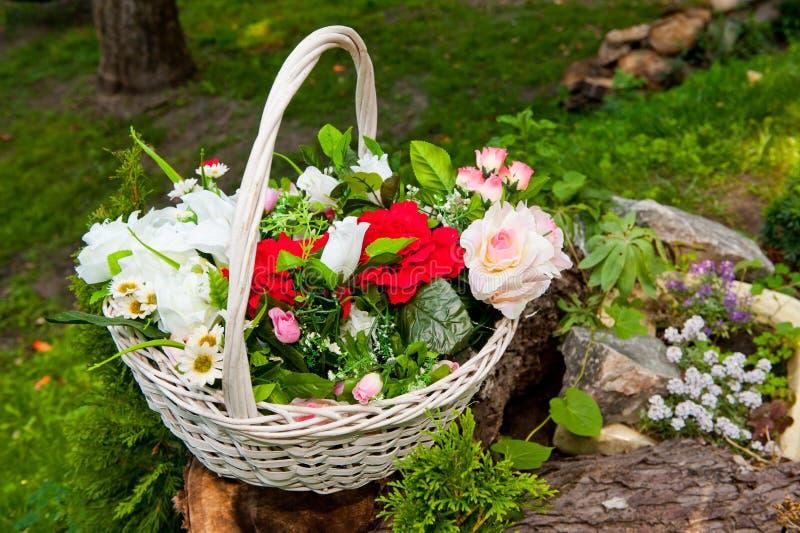 Canestro di vimini bianco con i fiori artificiali luminosi fotografia stock libera da diritti