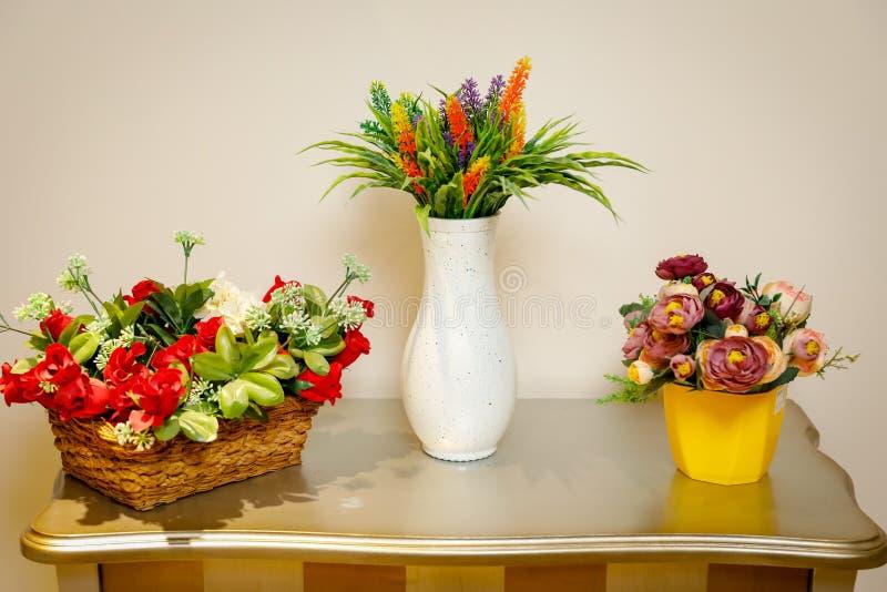 Canestro di vimini con i fiori decorativi Vaso bianco con i wildflowers Vaso giallo con i fiori sulla tavola fotografia stock libera da diritti