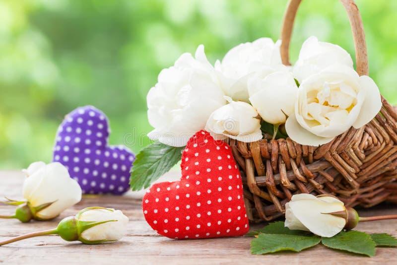 Canestro di vimini con i fiori rosa selvaggi e due cuori fotografie stock libere da diritti
