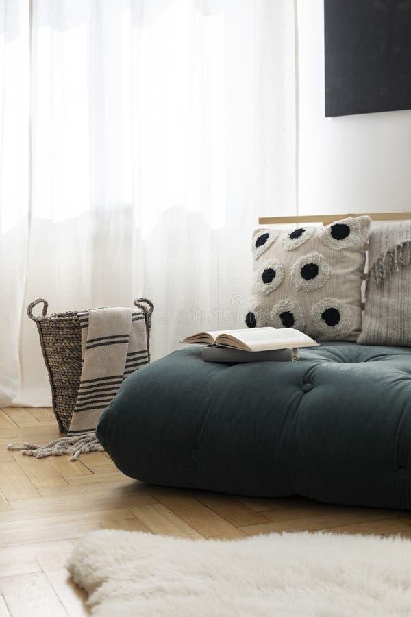 Canestro di vimini con la coperta a strisce accanto al futon verde del muschio con i cuscini ed il libro aperto, tappeto bianco d fotografie stock