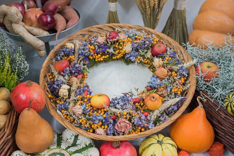 Canestro di vimini con la corona autunnale su una tavola di ringraziamento fotografie stock