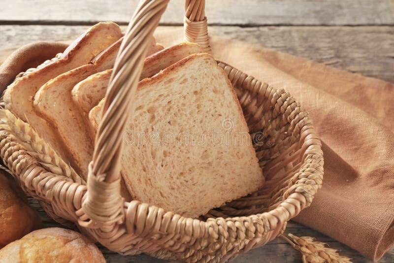Canestro di vimini con pane ed i panini affettati freschi fotografia stock libera da diritti