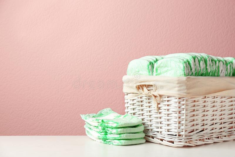 Canestro di vimini e pannolini eliminabili sulla tavola contro il fondo di colore, spazio per testo fotografie stock libere da diritti