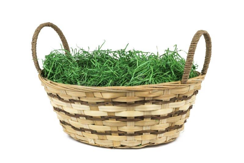 Canestro di vimini di Pasqua con erba verde su fondo bianco isolato immagini stock libere da diritti