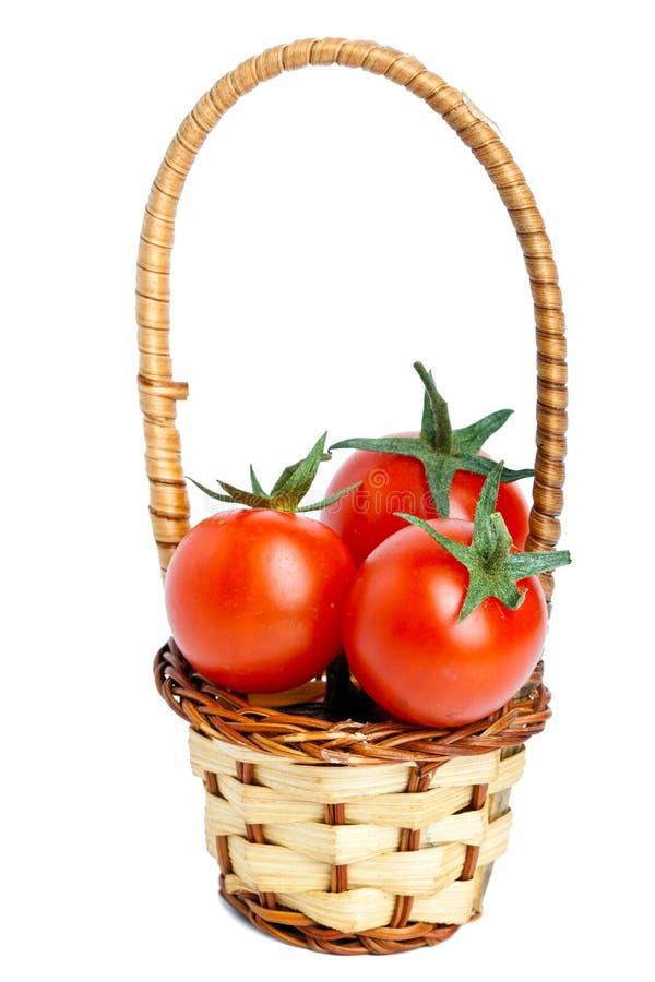 Canestro e tre pomodori fotografie stock libere da diritti