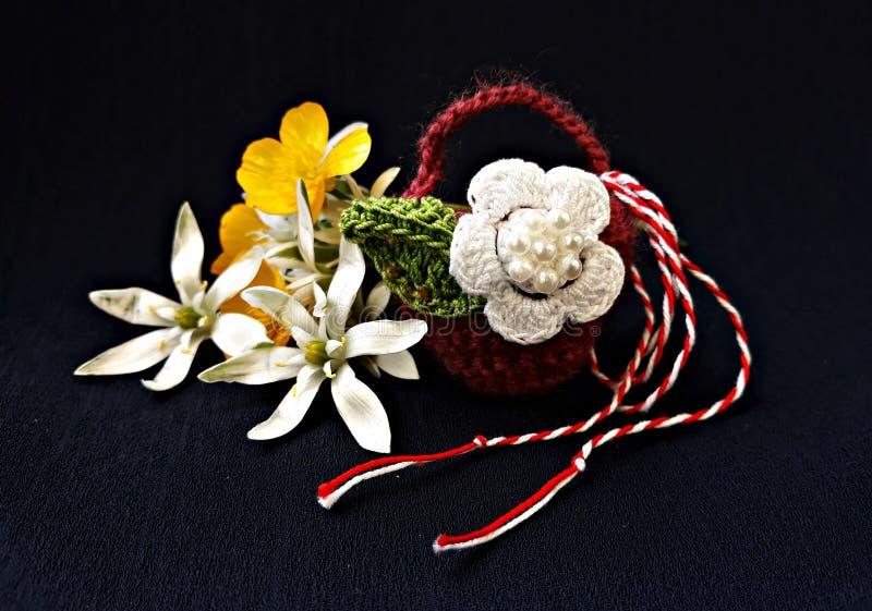 Canestro a foglie rampanti fatto a mano con i fiori della molla e la corda rossa e bianca, conosciuti come Martisor immagine stock libera da diritti