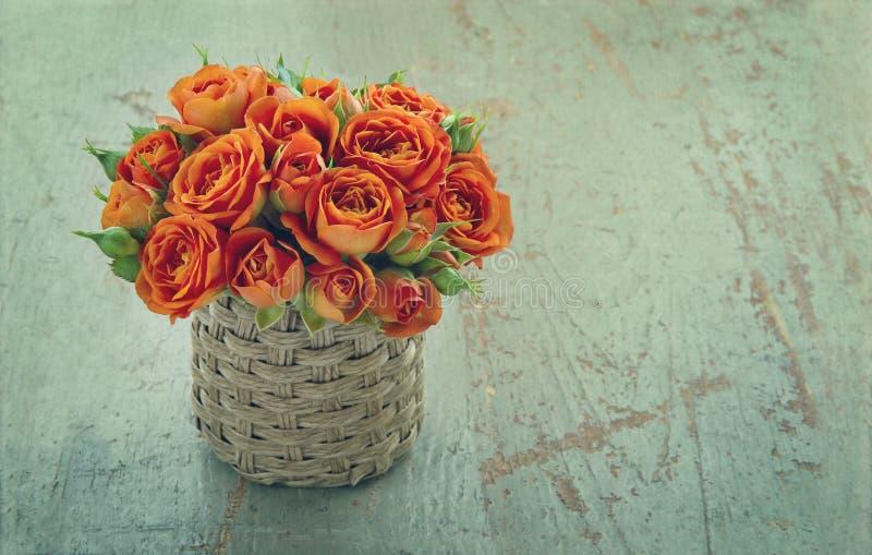 Canestro in pieno delle rose arancio su fondo di legno immagini stock libere da diritti