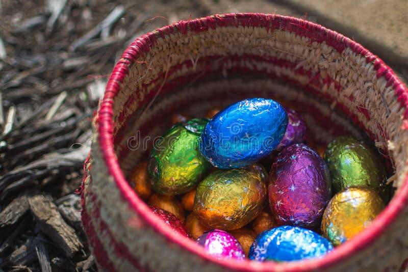 Canestro in pieno delle uova di Pasqua in imballaggio leggero brillanti del cioccolato immagini stock libere da diritti
