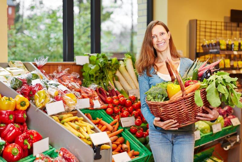 Canestro sorridente della tenuta della donna con le verdure immagine stock libera da diritti
