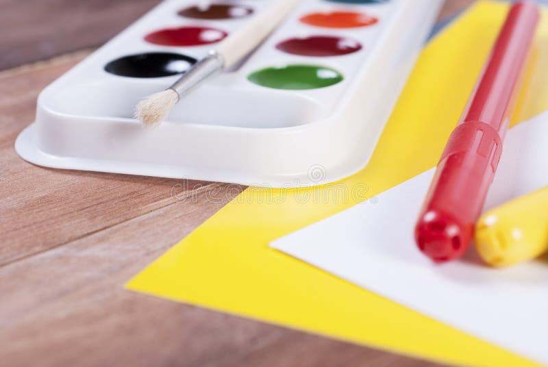 Canetas com ponta de feltro em um fundo das pinturas e do papel colorido fotografia de stock