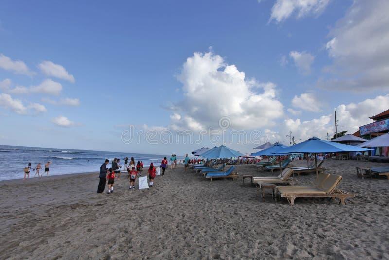 Canggu Indonesien - Maj 27, 2019: Den turist- tyckande om soliga dagen i stranden och lokala studenter sammanfogar strandlokalv?r arkivfoton
