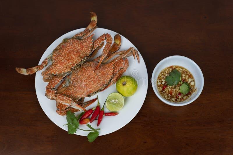 Cangrejos azules con la salsa de inmersión tailandesa de los mariscos en una placa, en una madera imágenes de archivo libres de regalías