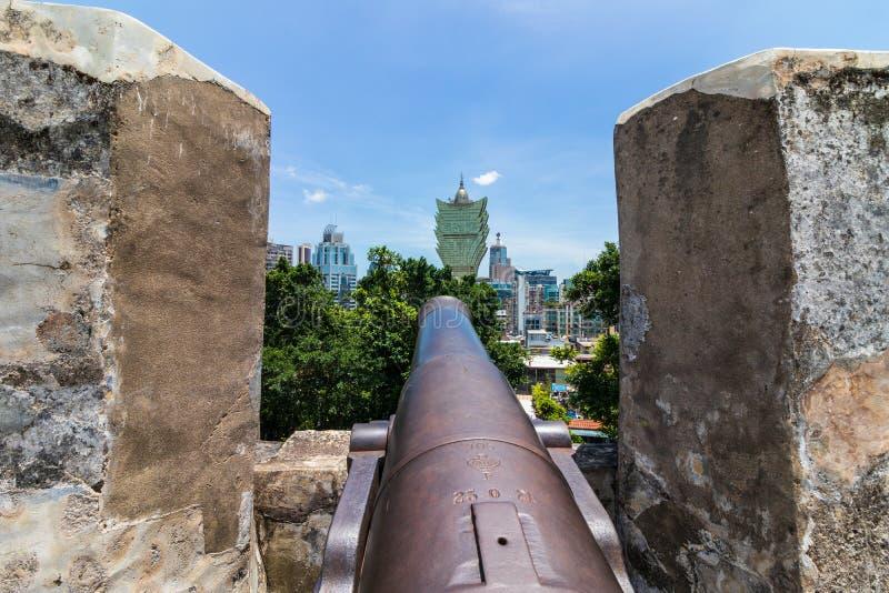 Canhão da réplica e parede da defesa da fortaleza da montagem, a Fortaleza do Monte, skyline de Macau no fundo Santo António, Mac fotos de stock royalty free