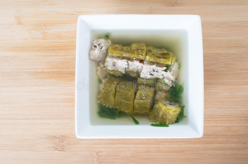Canh kho qua nhoi thit. Vietnamese stuffed bitter melon soup, canh kho qua nhoi thit against wooden board background stock photos