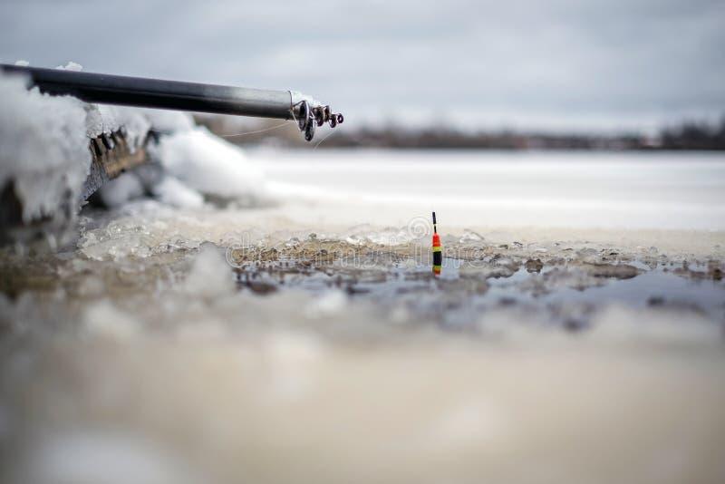 Canna da pesca con il galleggiante su ghiaccio immagini stock