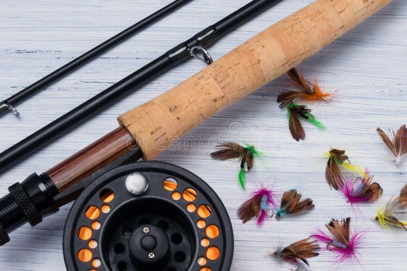 Canna da pesca con la bobina e varie esche per la pesca del primo piano immagine stock