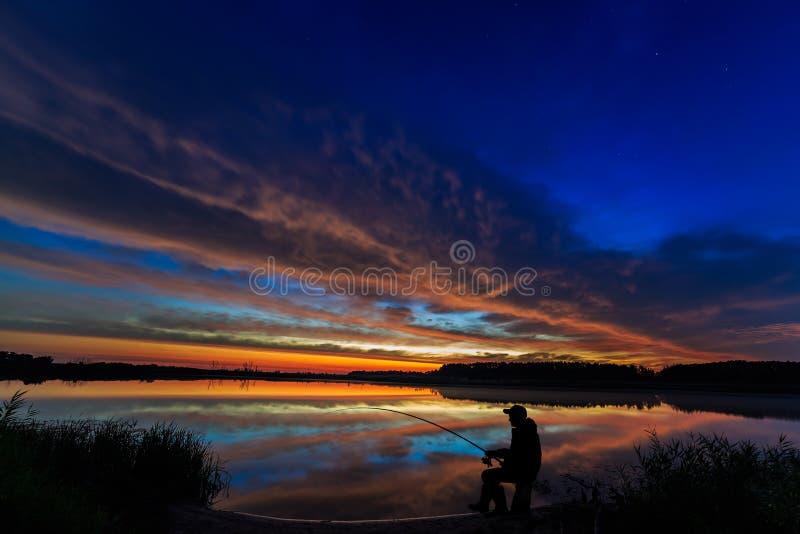 Canna da pesca del pescatore all'alba sul lago immagine stock libera da diritti