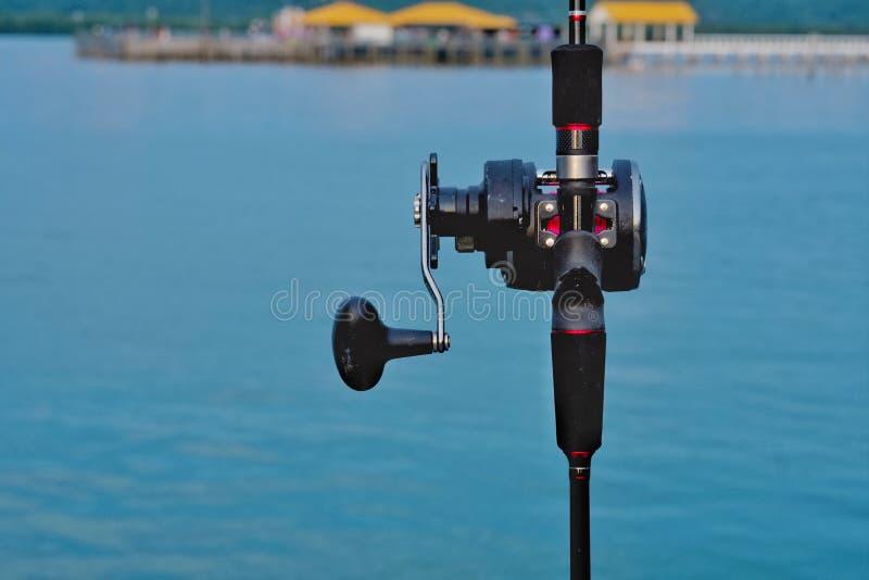Canna da pesca e mano della canna da pesca con il mare nel fondo fotografie stock