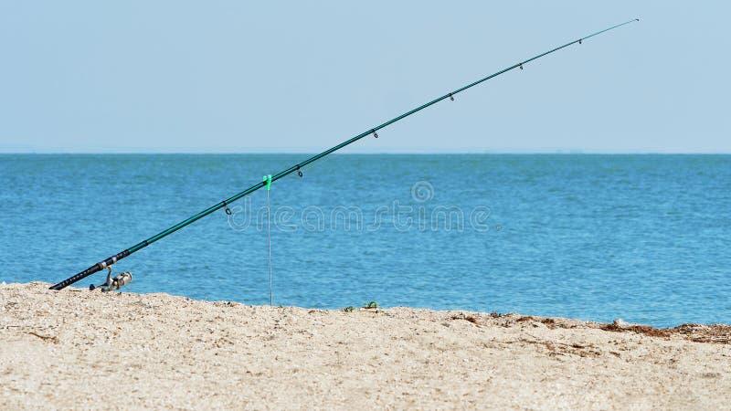 Canna da pesca sulla riva di mare fotografia stock